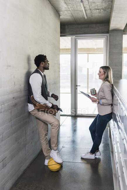 Gelegenheitsunternehmer und Geschäftsfrau diskutieren auf Büroflur — Stockfoto