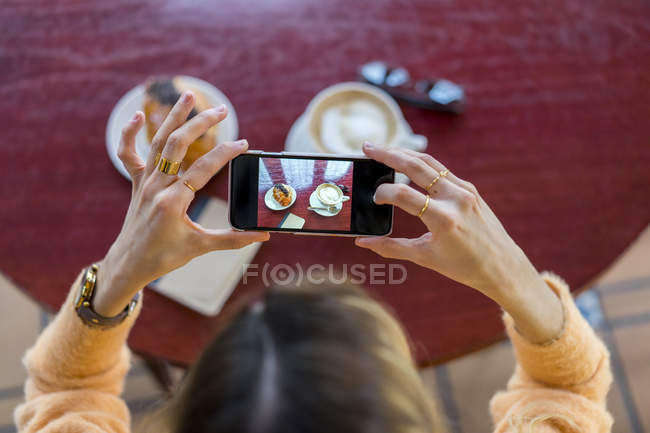Overhead view of woman in a cafe taking cell phone picture — Stock Photo