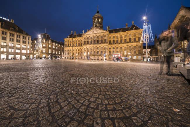 Нидерланды, Голландия, Амстердам, Дам-сквер с Палеис оп де Дам ночью — стоковое фото