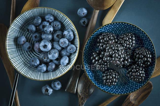 Cuencos de arándanos frescos y moras sobre fondo azul oscuro con cucharas de madera - foto de stock