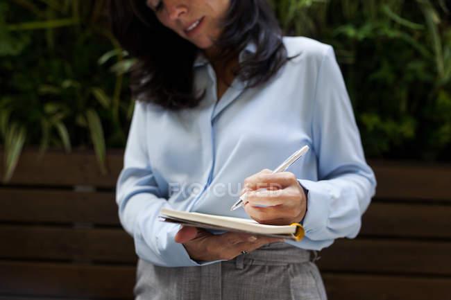 Крупний план ділової жінки беручи нотатки — стокове фото