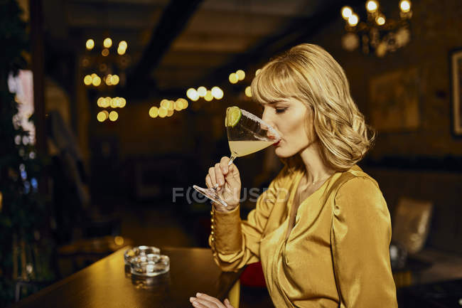 Elegant woman drinking cocktail in a bar — Stock Photo