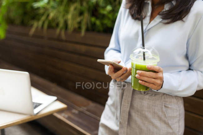 Businesswoman holding smoothie using cell phone in garden cafe — Stock Photo