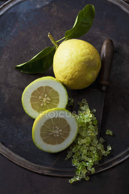 Свіжий цілий лимон і шматочки на темному тлі грандж з ножем і пальцями вапна штук — стокове фото