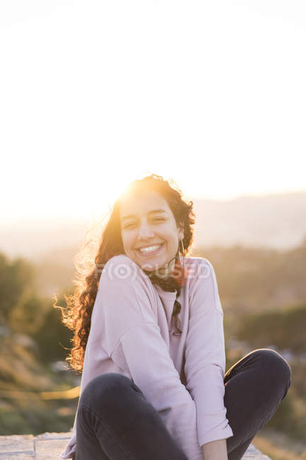 Ritratto di giovane donna felice con i capelli lunghi seduta su un muro al tramonto — Foto stock