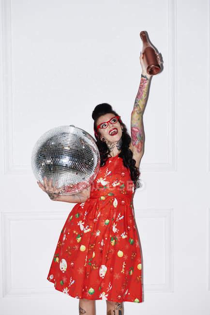 Портрет татуированной женщины с бутылкой шампанского и диско-шаром — стоковое фото