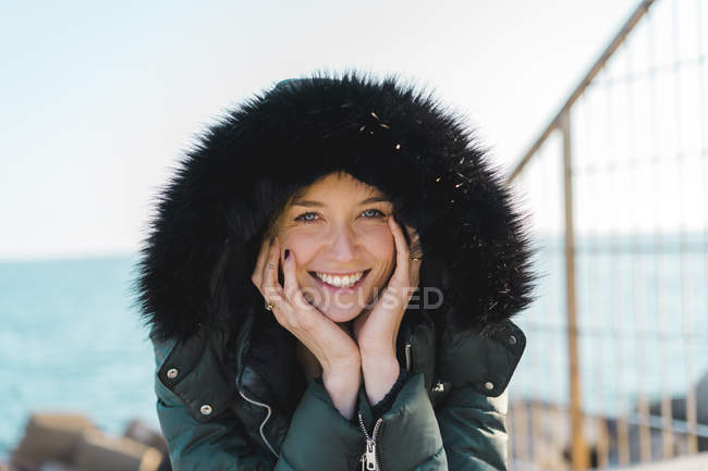 Portrait of happy woman with head in her hands wearing hooded jacket — Foto stock