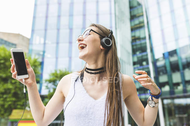 Happy teenage girl with cell phone and headphones in the city — Stock Photo