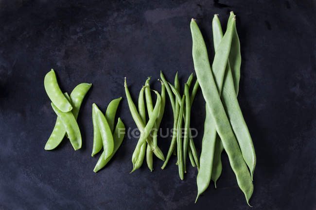 Various sorts of beans and peas on dark metal — стокове фото