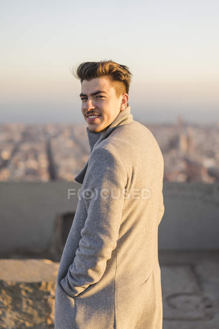 Portrait of smiling young man wearing grey coat at sunset — Photo de stock