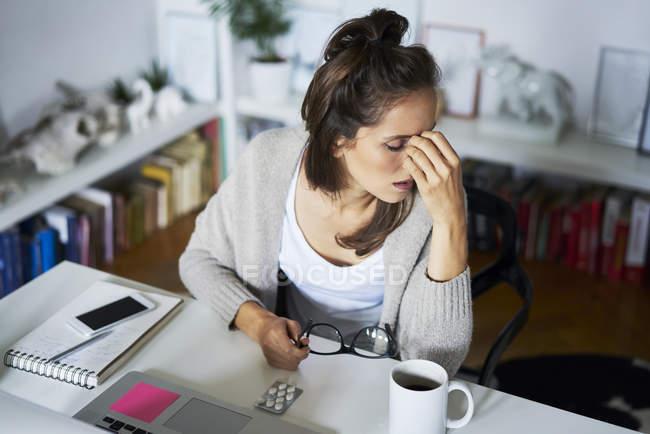 Молодая женщина, сидящая дома за партой, страдает головной болью — стоковое фото