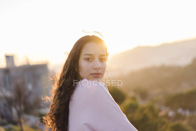 Portrait of young woman with long curly hair at evening twilight — Stock Photo