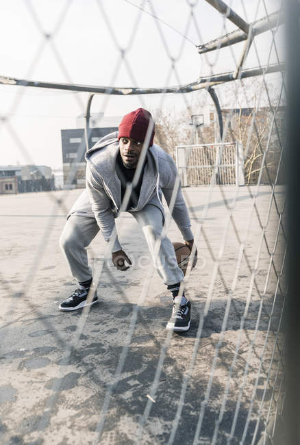 African american Basketball player in action on court behind fence — Stock Photo