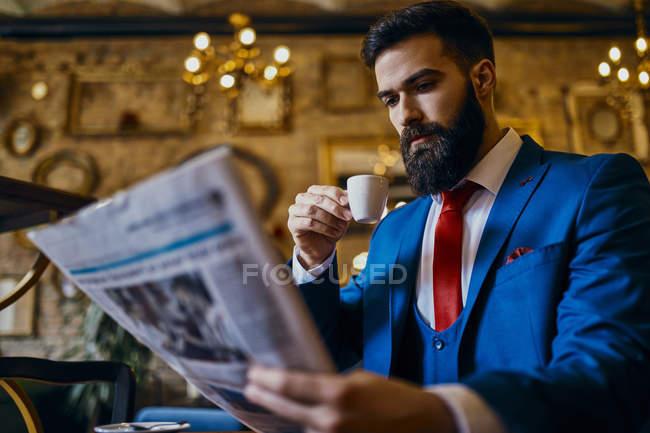 Элегантный мужчина пьет кофе и читает газету в кафе — стоковое фото