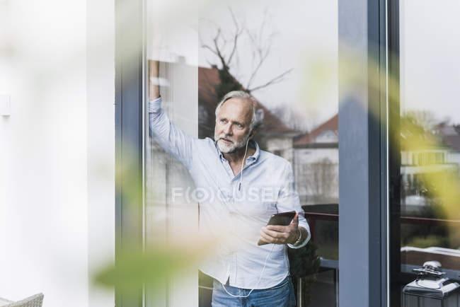 Uomo maturo che ascolta musica con auricolari e tablet, guardando fuori dalla porta della terrazza — Foto stock