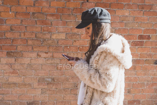 Stylish young woman in front of brick wall and using cell phone — Stock Photo