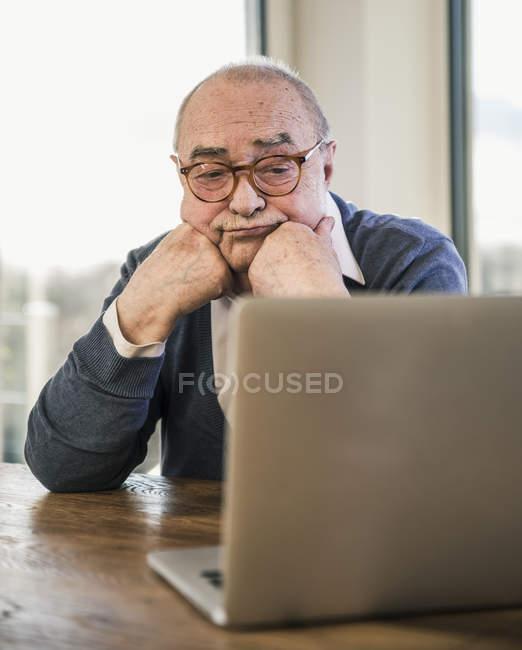 Homme aîné s'asseyant à la table et regardant l'ordinateur portatif — Photo de stock