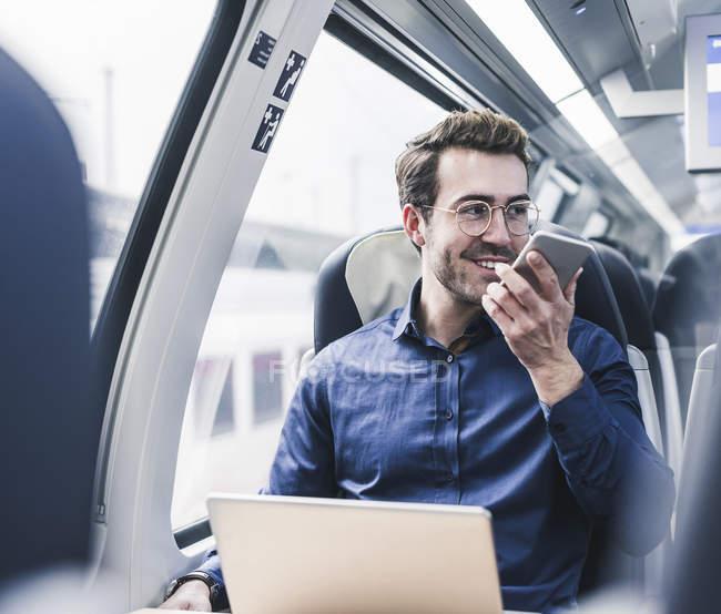 Homme d'affaires souriant dans le train en utilisant un téléphone portable — Photo de stock