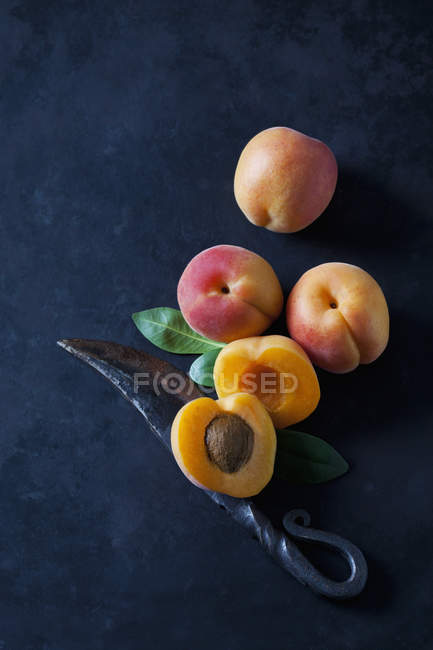Fresh whole and halved peaches on dark grunge background with knife — Stock Photo