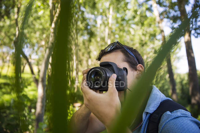 Man taking photos in forest with camera - foto de stock