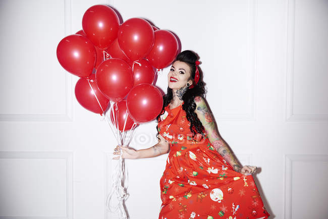 Portrait of tattooed woman with bunch of red balloons — Stock Photo