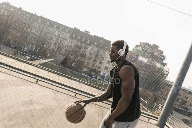 African american Basketball player with headphones in action on court — Stock Photo