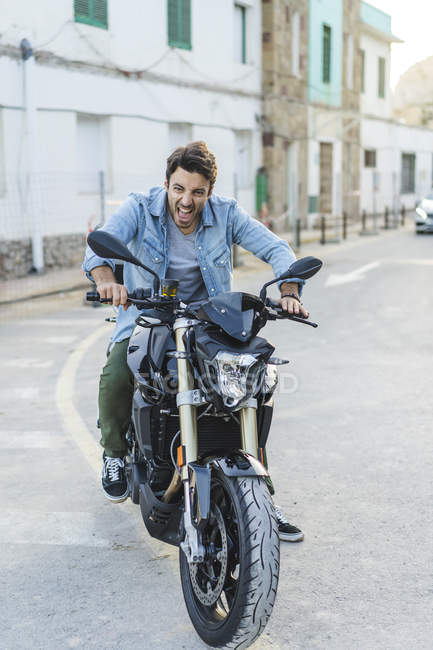 Portrait of screaming young man sitting on motorbike and pulling funny faces — Stock Photo