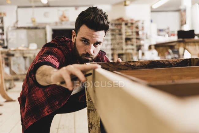 Человек осматривает дерево в мастерской — стоковое фото