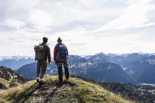 Austria, Tyrol, young couple standing in mountainscape and looking at view — Stock Photo