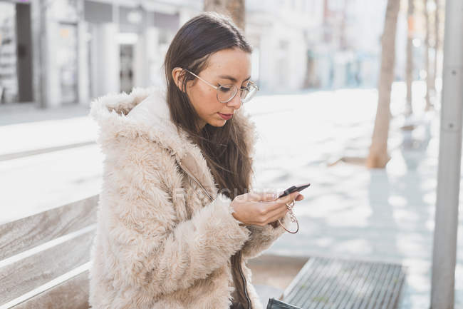 Stylish young woman in the city using cell phone — Stock Photo