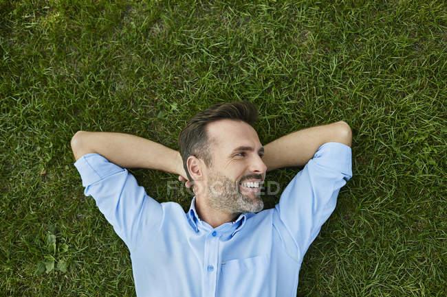 Homme relaxant sur prairie, vue dégagée — Photo de stock