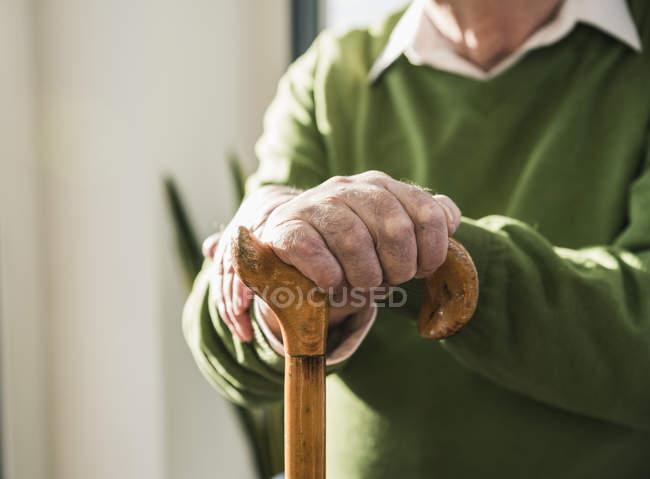 Plan rapproché de l'homme aîné s'appuyant sur la canne — Photo de stock