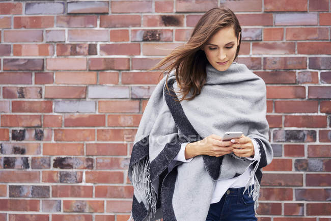 Smiling young woman looking at cell phone in front of brick wall — Stock Photo