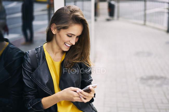 Счастливая женщина смотрит на мобильный телефон — стоковое фото