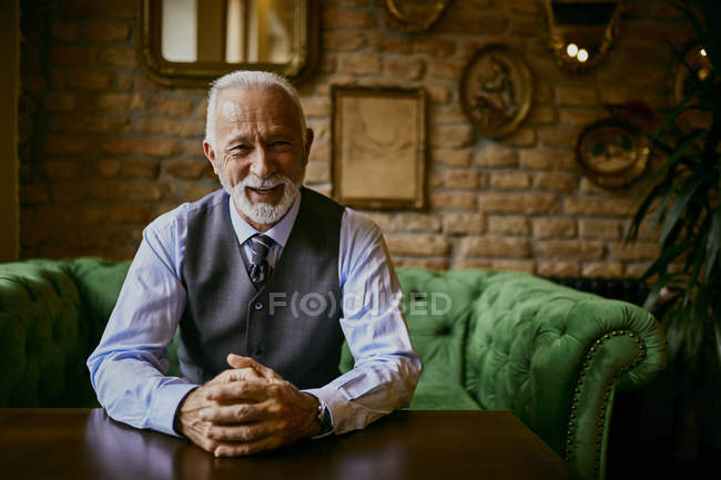 Portrait of elegant senior man sitting on couch in a cafe and smiling — Stock Photo