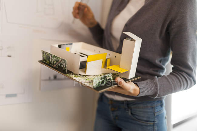 Female architect working on a project, holding architectural model — Stock Photo