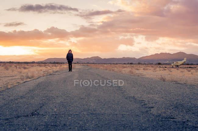 EE.UU., California, Joshua Tree, joven camina a lo largo de un camino mientras se pone el sol - foto de stock