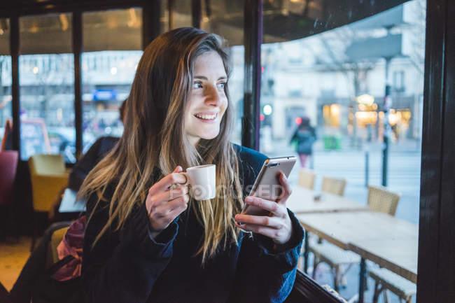 París, Francia, retrato de una joven sonriente con smartphone bebiendo espresso en una cafetería - foto de stock