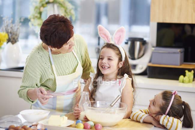 Nonna e nipoti che cucinano biscotti pasquali in cucina insieme — Foto stock