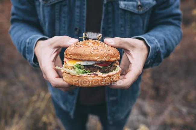 Imagen recortada de hombre sosteniendo hamburguesa - foto de stock