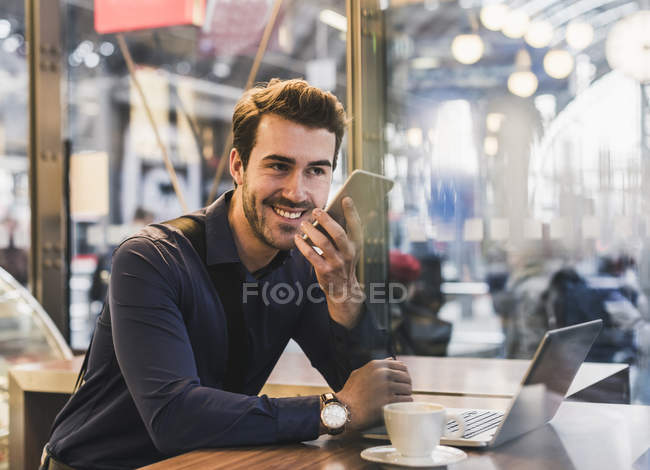 Smiling young businessman in a cafe at train station with cell phone and laptop — Stock Photo