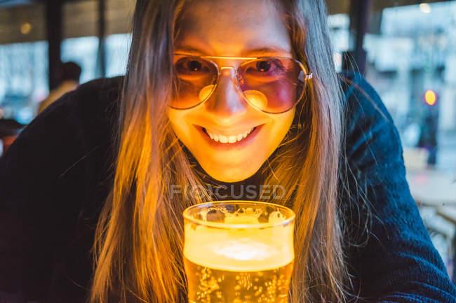 Париж, Франция, портрет счастливой молодой женщины с бокалом пива в пабе вечером — стоковое фото