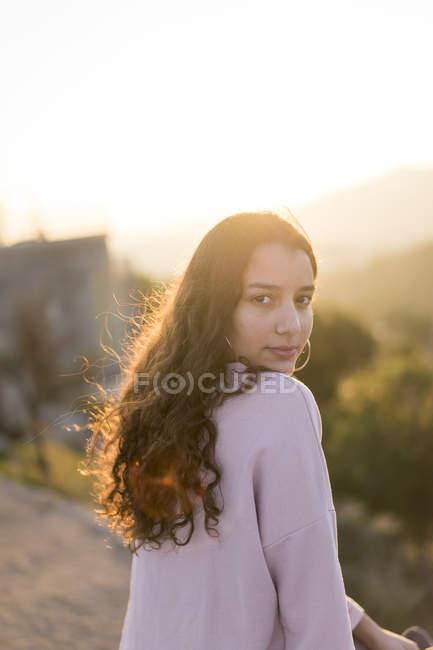 Ritratto di giovane donna con lunghi capelli ricci al tramonto — Foto stock