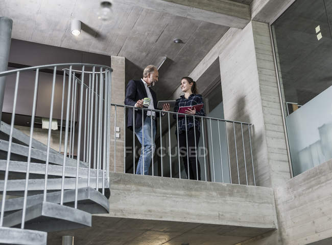 Smiling mature businessman and young woman talking on staircase — Stockfoto
