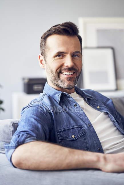 Portrait d'un homme souriant assis sur un canapé — Photo de stock