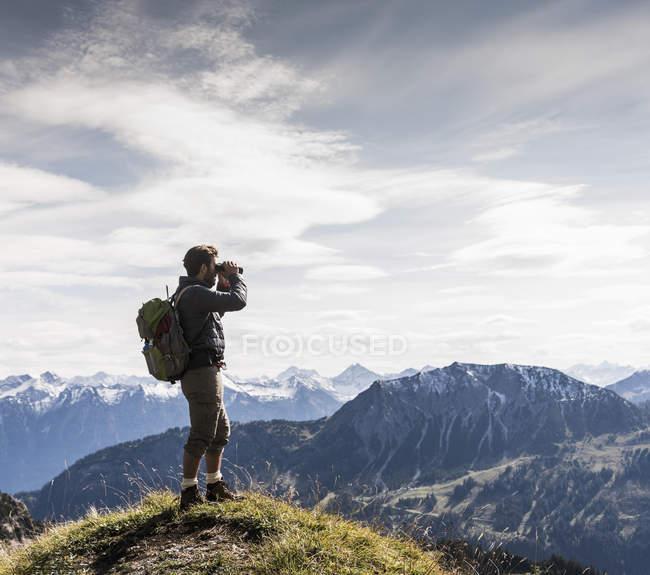 Austria, Tirol, joven de pie en el paisaje de montaña mirando a la vista con prismáticos - foto de stock