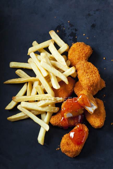 Chicken Nuggets mit süßer Chilisoße und Pommes auf dunklem Grund — Stockfoto