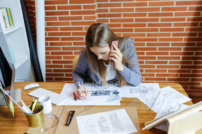 Young woman working in architecture office, talking on the phone — Stock Photo