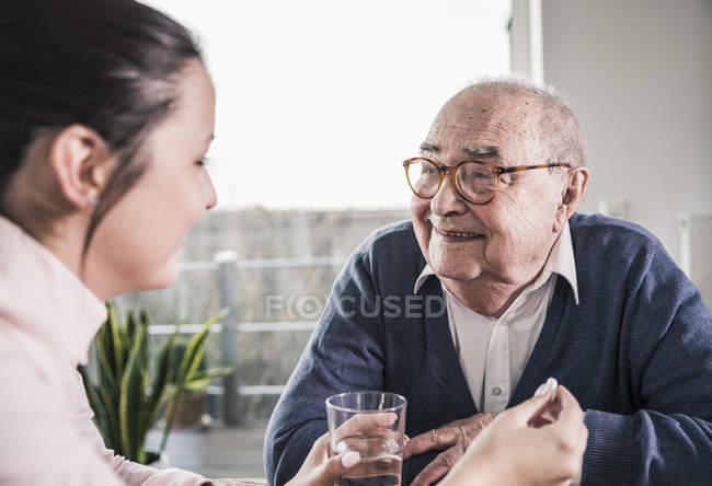 Женщина с таблеткой и стаканом воды для улыбающегося пожилого мужчины — стоковое фото