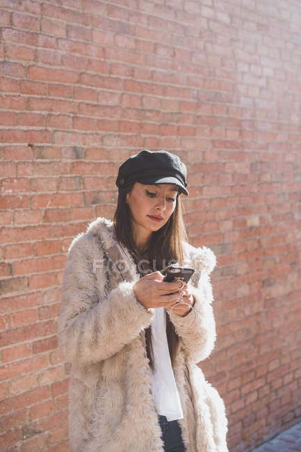 Stylish young woman in front of brick wall using cell phone — Stock Photo